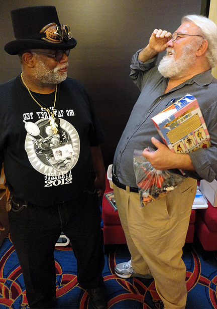 "E.J. White (l) charming an attendee at this year's Joelanta event in Atlanta, GA.In honor of the show's ""Chronus Adventurer"" exclusive, E.J. was sporting an 1880s top hat with exotic, ""steampunk"" goggles."