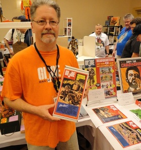 Graphic Designer and Illustrator extraordinaire, David Howard, poses with a few of his reproduction and custom GIjOE boxes, plus posters and related artwork during the recent Joelanta 2012 show in Atlanta, GA. (Photo: Mark Otnes)