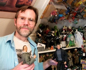 Wayne Faucher poses in his home studio recently with a couple of his custom figures.