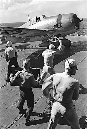 Navy flight deck crewmen prepare to launch an F6F Hellcat fighter plane off an aircraft carrier during WW2. (Photo: US Navy)