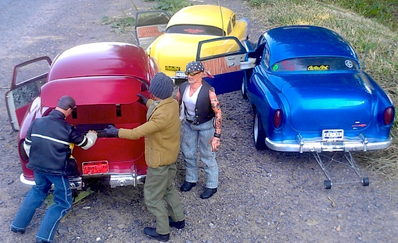 "Three of Ron Stymus' custom figures (his 'mini-me' is the one on the right) prepare to go cruising in three of his brightly-painted 1:6 scale customized ""hot rods,"" (Photo: Ron Stymus)"