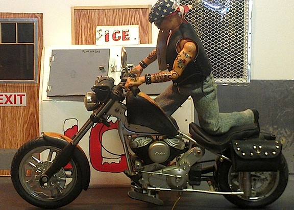 "Ron's ""Mini Me"" prepares to take a ride on his 1:6 scale customized chopper. Note the hand-made background including a 1:6 ice freezer, walls door and window. Outstanding! (Photo: Ron Stymus)"