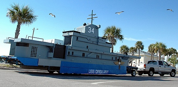 Continually maintained by volunteers since its construction in 1955, the massive USS Oriskany parade float ship is still utilized in annual parades in Pensacola, FL. Note how it dwarfs the extended-cab pickup truck struggling to tow it! (Photo: