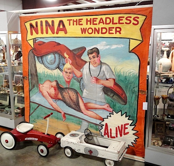"""Searching for anything as small as a GIjOE at a flea market is much like looking for a needle in a haystack. But by applying various teamwork strategies, members of GIjOE collector clubs can efficiently """"canvas"""" the giant sale events. This giant, hand-painted, vintage """"freak show"""" banner heralding """"Nina, the Headless Wonder"""" was visible to everyone from hundreds of yards away. Unfortunately, GIJoes are MUCH harder to locate. (Photo: Mark Otnes)"""