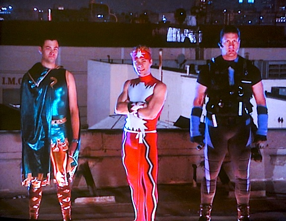 "Now THIS is good television! Three handsome heroes in brightly colored spandex, standing on the rooftop of the secret ""lair,"" waiting for their fates to be decided by none other than Stan ""The Man"" Lee. Cool! (Photo: Syfy)"