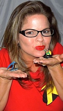 "Tina even changes costumes when posing with different products. Here, shes dons a tight red ""Robin"" T-shirt and and pair of black-framed glasses (to simulate his mask) while holding up tiny figurines of Batman and Robin. (Photo: Smileygirl2012)"