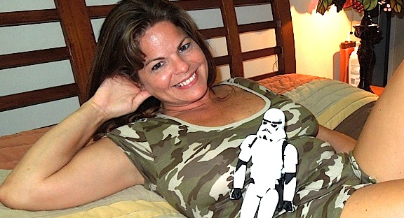 "Tina ""Smileygirl2012,"" a well-regarded GIjOE dealer on ebay, poses recently with a 12-inch Stormtrooper, wearing little more than her T-shirt and a smile. ""Use the FORCE, Luke!"" (Photo: Smileygirl2012)"