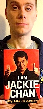 "Stork holds up his autographed copy of the autobiography of his idol, Jackie Chan. According to John, ""He was my biggest hero growing up. Jackie Chan's at the root of it all for me."" (Photo: John Stork, exclusive to The Joe Report)"