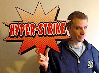 "Stork holds up the sign that was mounted on his bed in the ""lair"" during the show. He was allowed to keep it and his Stan Lee-designed costume as souveniers of the show. (Photo: John Stork)"