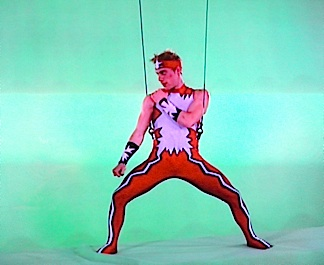 "Stork performing flips and stunts while hanging from suspension wires in front of a special effects ""green screen."" With all of his previous circus experience, it was (as he earlier predicted), ""a piece of cake."" (Photo: Syfy)"