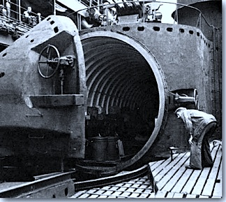 In this WWII image, an American sailor inspects the sub's massive, open hanger door that leads to the interior of the ship where the bomber seaplanes were stored. (Photo: US Navy)