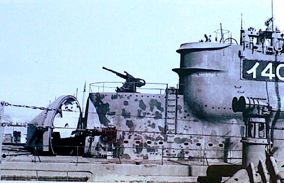 "This WWII photo shows the battle-scarred deck and conning tower of a captured Imperial Japanese I-400 class submarine, with its ""game-changing"" water-tight hangar door (located just forward and below the deck gun) shown in its surfaced, open position. Bomber seaplanes (stored inside) would exit, attach to a catapult, and launch from the sub to attack targets both at sea and on land. For retrieval, the aircraft would rendevoux with the sub and be lifted aboard with the ship's crane (not shown). (Photo: US Navy)"