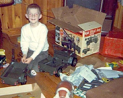 "We suspect that if a study was done, the GIjOE 5-Star Jeep may have been one of the most photographed toys EVER. In this great shot, ""Mike"" looks up from his idyllic work assembling his Jeep for the first time, Christmas morning, 1965. (Photo: Alphadogs)"