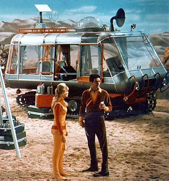 "Don West and Judy Robinson discuss where they can go to be alone (""I think I saw a good spot behind that rock, Judy), while the far more famous, ""Space Chariot"" waits patiently in the background of this scene from ""Lost in Space."" (Photo: CBS)"