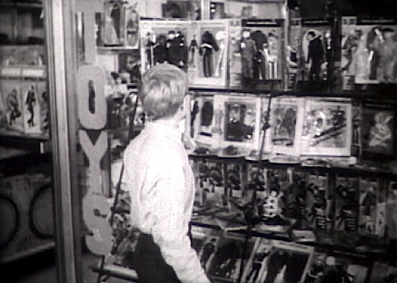 "The first commercial opens with a wide shot of O'Keefe walking by a toy store window filled with racks of GIjOEs, equipment cards, and window-boxed uniform sets. As he walks, he sings ""GIjOE, GIjOE, Fighting man from head to toe..."" (Photo: Matt McKeeby)"
