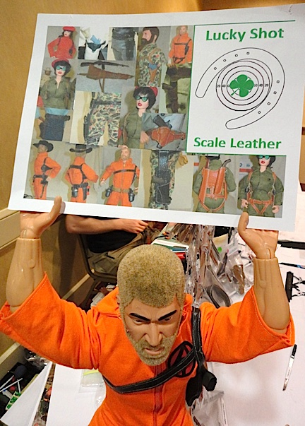"A giant ""Men of Honor"" action figure customized into an oversized Air Commander (humorously) holds up a poster showing various gun rigs and other 1:6 creations offered from Aaron's ""Lucky Shot Scale Leather."" (Photo: Mark Otnes)"