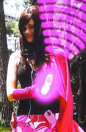 In this screenshot from the show, Chelsea is seen for the first time as she emerges from the limosine and opens her trademark cell phone, emitting waves of superhero power! (Photo: Syfy)