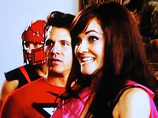 "Chelsea reacts along with fellow contestants Chris Watters and E. Quincy Sloan as Stan Lee suddenly appears on a nearby monitor accusing them of NOT behaving like superheroes. From this moment on, contestants learned they were being judged ""at all times"" and that behavior considered to be ""unheroic"" could get them eliminated. (Photo: Syfy)"