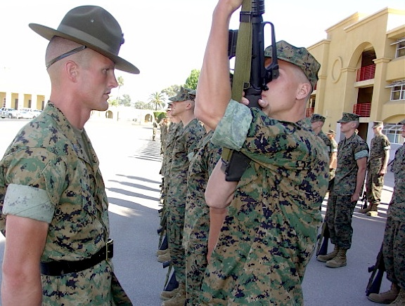 "In this file photo, a US Marine Corps Drill Instructor (left) watches as a new recruit or ""puke"" goes through the various steps and procedures required for proper ""Inspection Arms."" (Photo: USMC)"