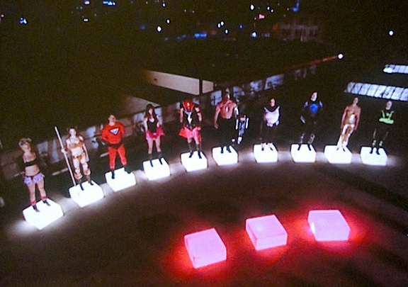 """In a stroke of brilliance, the show's creators came up with Stan's (very) tele-visual """"cubes of elimination."""" At night, the internally-lit cubes were dramatically effective in setting a mood and communicating two simple facts: Standing on a red cube meant you were facing final elimination. Standing on a white cube meant you were """"safe""""—for now. (Photo: Syfy)"""
