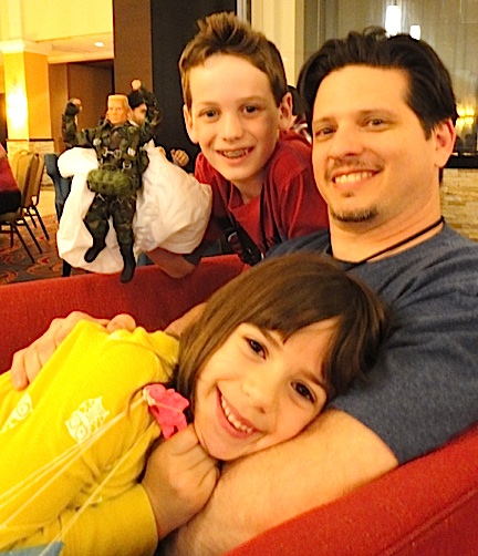 "Passing the torch— GIjOE fan and toy dealer, Ryan Bonavia (r), with his children Logan (11) and Ella (6), waiting for the beginning of Joelanta 2014's ""Parachute Drop."" (Photo: Mark Otnes)"