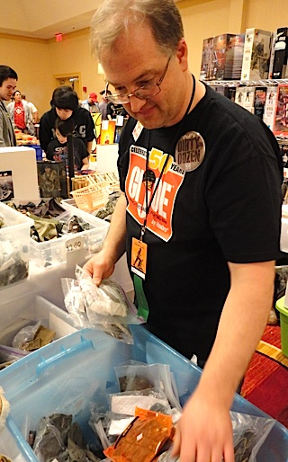 Dirty Dozen member, Brad Curry, looks through bins for German uniform pieces while taking a break from handing out free samples of PoP Rocks candy. (Photo: Mark Otnes)