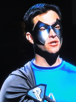In this screenshot from Who Wants to be a Superhero?, Williams replies to questions from Stan Lee while wearing Parthenon's original mask. The mask did not last long on the show.