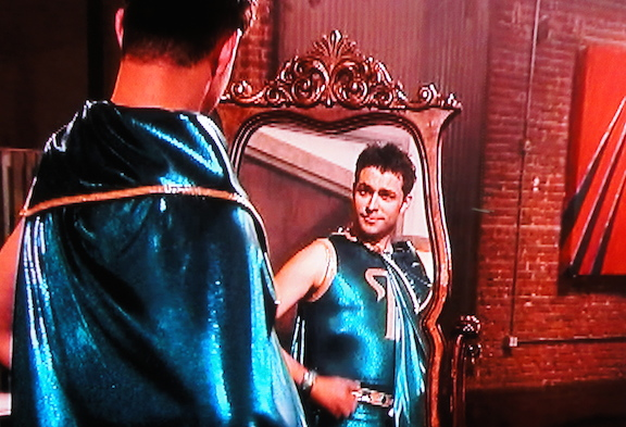 """Despite saving his original """"wash-n-wear"""" costume from the honey of """"Bee-Sting,"""" Williams had to turn it in for a costume created by Stan Lee and provided by the show. Here, he looks at it in a mirror for the first time. (Photo: Syfy)"""