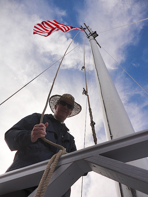 "In a view afforded to a lucky few, volunteer ""flag master,"" Brian Reynolds prepares to hand me the lanyard to which I would clip my flag and then joyfully raise it up the giant flagpole. You cannot imagine the excitement! (Photo: Mark Otnes)"