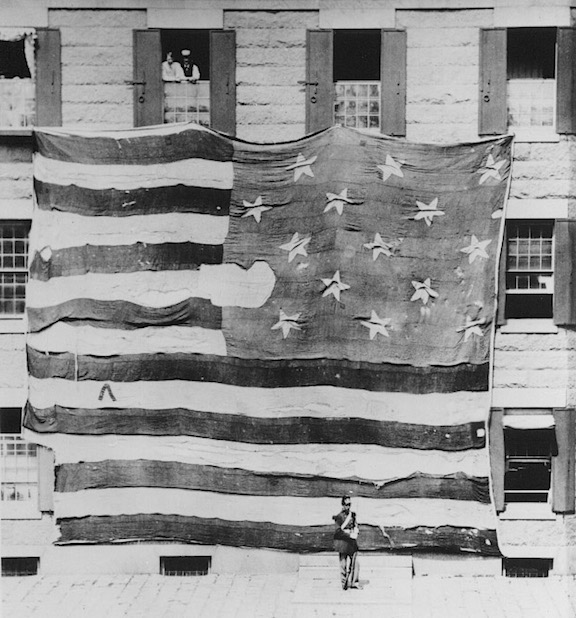 This is the first-known photo ever taken of the Star-Spangled Banner, in 1873. As you can see, after almost 60 years, souvenir hunters had cut much of its length away, as well as a sizable chunk of its blue field as well. It would be many more years before such pilfering was finally halted and the remainder of the flag protected. (Photo: Smithsonian)