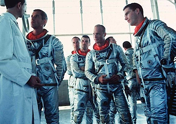 "Don't try and tell them where the explosive bolts go, or that they're just going to go along for the ride. In this scene from ""The Right Stuff,"" actors recreate one of many serious conversations astronauts held with NASA engineers regarding the construction and design of the Mercury and Gemini space capsules. (Photo: Wikipedia)"
